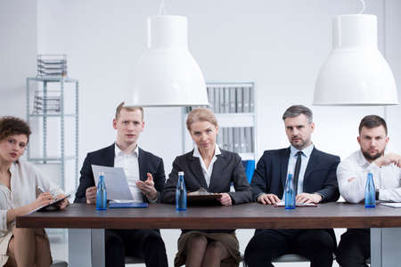 Professional businesswomen and businessmen listening to entrepreneur applying for subsidies for the company