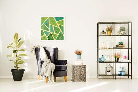 Heather et des livres sur une table métallique à côté de fauteuil et calice dans le salon confortable intérieur avec de la peinture verte Banque d'images - 96607830