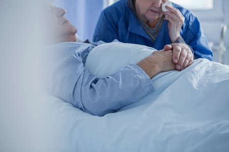 Crying woman wiping tears after died of husband in the health center 写真素材