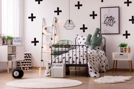 White round rug near bed with patterned blanket in scandinavian bedroom interior with poster and ladder