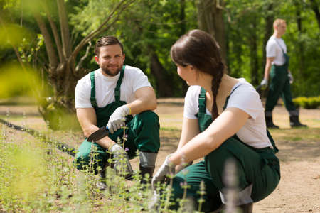 Two smiling young gardeners working in a sunny park