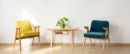 Simple living room interior with wooden table between yellow and blue armchairs against white wall Banco de Imagens