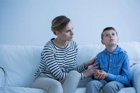 Autistic boy sitting on a sofa with his carer trying to calm him down Stock Photo