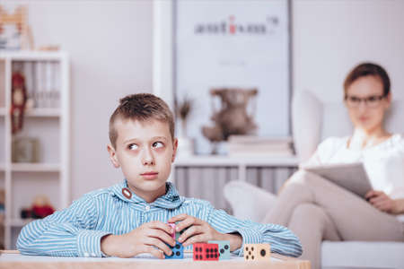 Autistic boy playing with colorful dice being watched by a psychotherapist sitting in the background Stockfoto