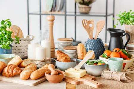 Close-up of dining table with fresh bread, croissants, candles, butter and tomatoes