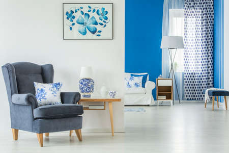 Pillow on armchair next to a wooden table with lamp in blue open space interior with poster on white wall Фото со стока