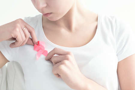 Close-up of woman fastening a pink, breast cancer ribbon to a white blouse