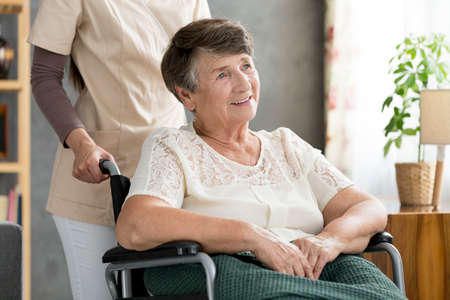 Smiling, disabled, elderly woman in a wheelchair supported by a nurse Stock Photo - 96879975