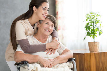 Caring and smiling woman hugging her happy grandmother in a wheelchair