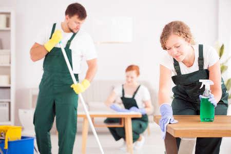 緑色のオーバーオールの女性は、洗浄洗剤を使用してテーブルを拭く