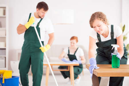 Woman in green overalls wiping table by using cleaning detergent
