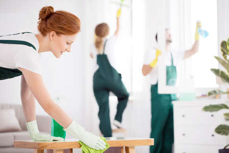 Professional cleaner wiping a table when cleaning a flat with her team