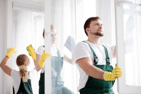 Cleaner in green overalls and yellow gloves washing windows in an apartment
