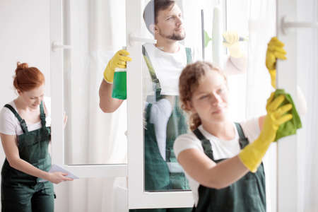 Skilled cleaning team washing the windows. Home cleaning service concept