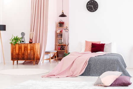 Feminine bedroom interior with pink blanket on gray bed and cabinet next to a walk-in closet