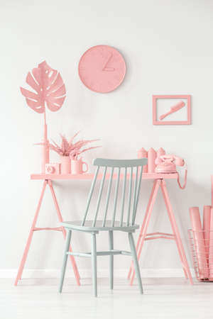 Blue chair at pink desk with fern against white wall with clock in creative home office interior