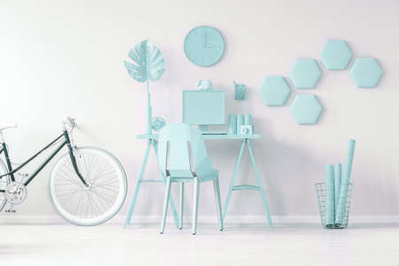 Blue workspace concept - black bicycle next to desk and chair against white wall with clock and honeycombs in blue workspace interior