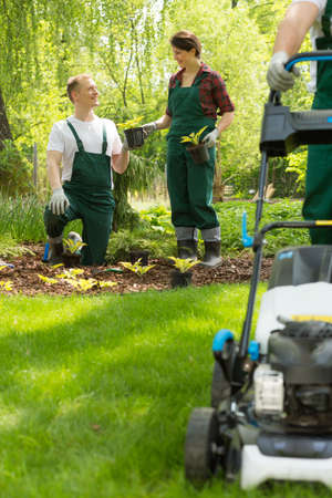 Blurry lawn mower next to a pair of young gardeners planting flowers
