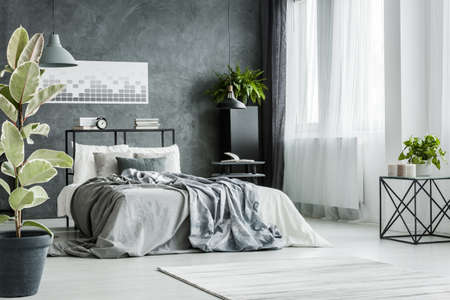 Double bed with gray sheets near the window in monochromatic bedroom interior