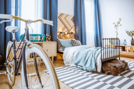 Close-up of bicycle in blue bedroom interior with drapes and suitcase under bed with lights