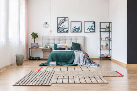 Comfortable king-size bed covered with green blanket standing in the bedroom interior next to a table
