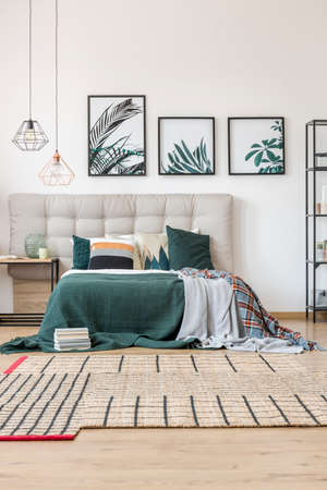 Cozy bedroom interior with king-size bed, dark green blanket and carpet