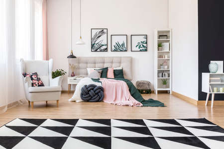 Black and white carpet with asymmetric patterns in front of double bed, armchair and white shelf in bedroom interior