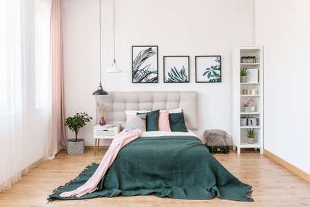 Modern bedroom interior with double bed, dark green blanket and botanical posters