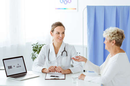 Elder woman talking with dietician about her health condition during control visit