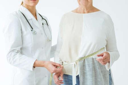 Nahaufnahmefoto der Frau mit Übergewicht während des Messens im Büro des Diätetikers Standard-Bild - 96666186