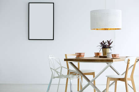 Mockup of empty poster in white dining room interior with lamp above wooden table Stock Photo