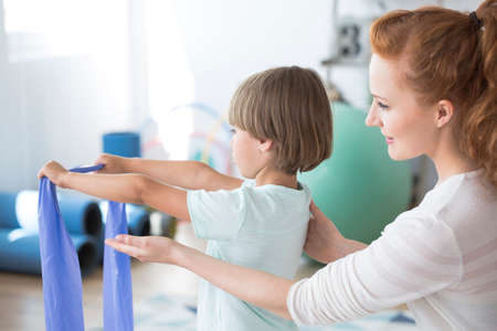 Physiotherapist supporting a kid stretching with violet elastic tape during corrective gymnastics Imagens