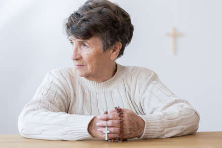 Religious grandmother in melancholy holding a rosary and praying in the church Banco de Imagens - 96666257