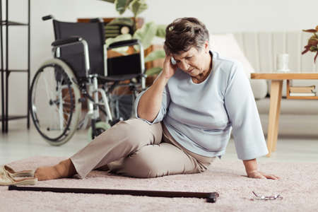 Senior woman with a headache sitting on the floor and looking for her cane after falling down. Wheelchair in the background