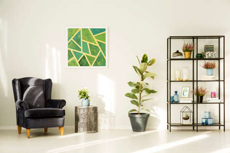 Dark armchair next to metal table and ficus in living room interior with green painting Stok Fotoğraf - 96880012