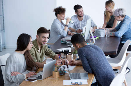 Cooperación entre compañeros de trabajo y empresaria trabajando en la puesta en marcha de una empresa moderna. Foto de archivo