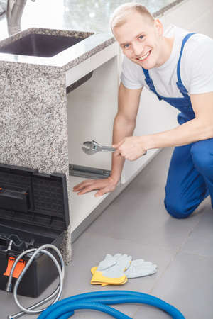 Young and handsome plumber smiling and holding a wrench while working in a kitchen Stock Photo