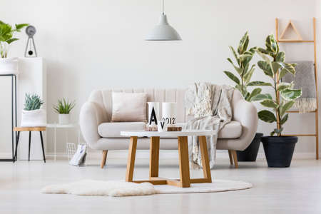 Wooden table with decorative jugs standing in the center of living room interior with bright couch