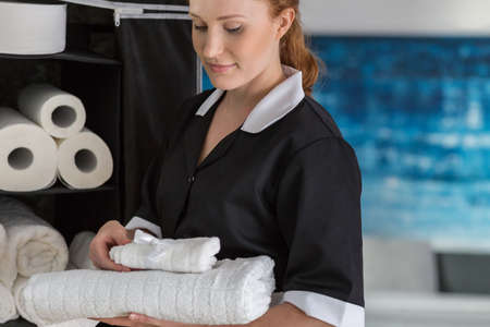 Smiling maidservant with white towels restocking bathroom cabinets Stock Photo