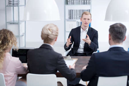 Young businessman talking to a management team in the company and explaining his project Stock Photo