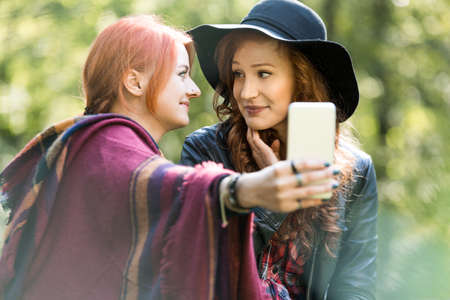 Two young woman taking a selfie in the forest