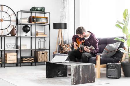 Muzyk siedzi na czarnej kanapie i gra na gitarze w nowoczesnym wnętrzu salonu.