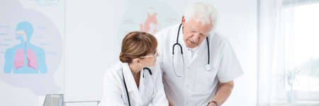 Elderly doctors with stethoscopes talking in a white medical center room