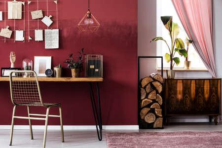 Armoire et bûches de bois à côté d'une chaise en métal au bureau avec horloge à l'intérieur de l'espace de travail