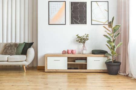 高いフィカスプラントとベージュのソファの間に立つ木製の食器棚を備えたエレガントなリビングルームのインテリア