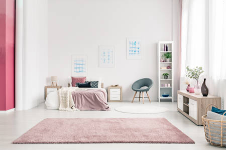 Pink carpet in spacious bedroom interior with grey chair next to bed against the wall with posters