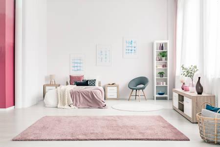 Rosa Teppich im geräumigen Schlafzimmerinnenraum mit grauem Stuhl nahe bei Bett gegen die Wand mit Plakaten