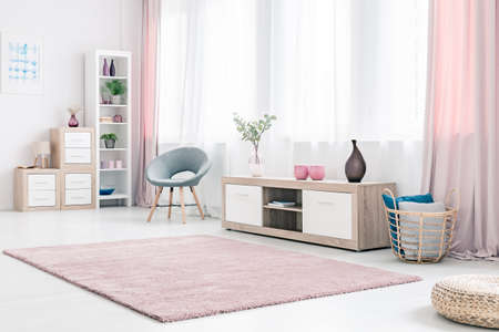 Grey armchair next to a wooden cupboard with dark vase in spacious, pink living room interior Stockfoto