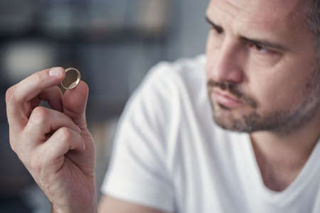 Disappointed man holding his wedding ring after divorce