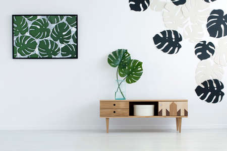 Wooden cupboard against the wall with monstera leaves poster and stickers in living room interior